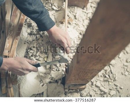 The hands of a young person using a hammer in a pile of rubble