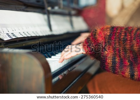 The hands of a young woman as she is playing the piano - stock photo