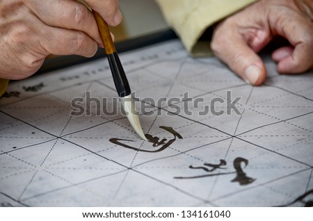 The hands of an elder person writing Chinese calligraphy - stock photo