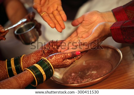 The hands of bride and groom being washed with holy water in a traditional Hindu wedding ritual - stock photo