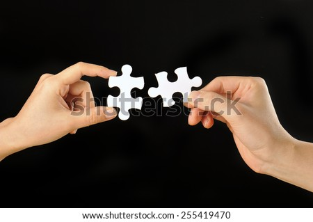 The hands of human beings that have a jigsaw puzzle that was taken with a black background - stock photo