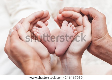 The hands of parents and the child's legs in the form of heart on a light background - stock photo