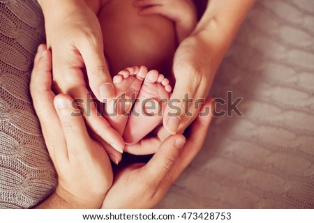 The hands of parents holding the feet of the baby. engagement rings. The child as a continuation of the wedding, family values