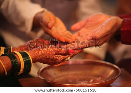 The hands of the bride and groom in a traditional Hindu wedding ritual