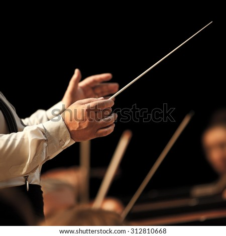 The hands of the conductor on the background of the orchestra in dark colors - stock photo