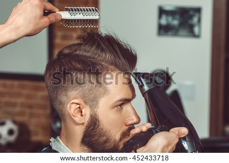 The hands of young barber making haircut of attractive bearded man in barbershop