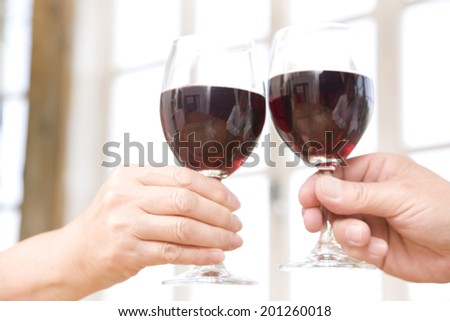 The hands toasting in red wine