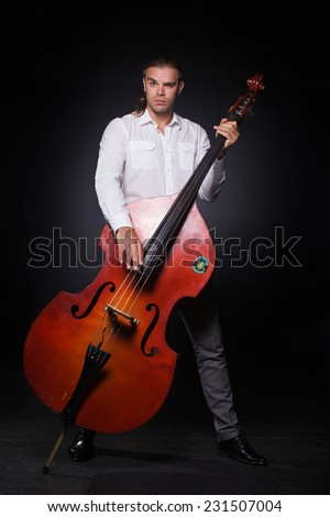 The handsome man is play music jazz on the contra bass - stock photo