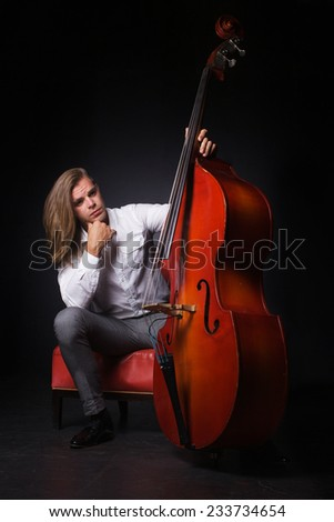 The handsome man with long hair is hold double-bass - stock photo