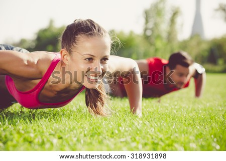 The handsome sportsman and the attractive woman doing some push ups in color effect  - stock photo