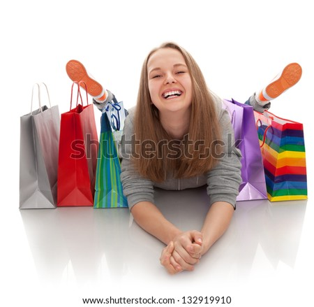 The happy attractive teenager girl lying with bags for purchases on a white background