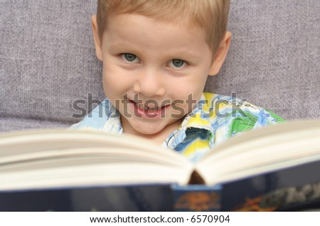 The happy boy holds the greater book in hands