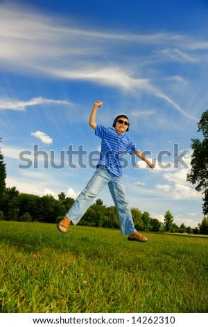 The happy boy in headphones jumps-2 - stock photo