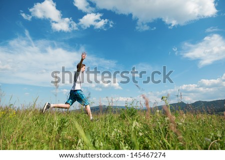 The happy boy runs on a green meadow - stock photo