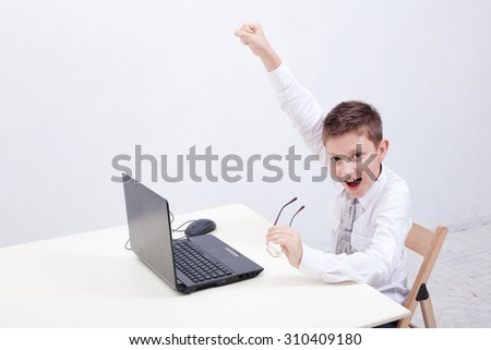 The happy  boy using his laptop computer on white background. - stock photo