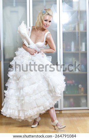 The happy bride tries on a wedding dress - stock photo