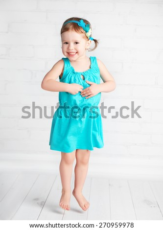 the happy child little girl jumping for joy - stock photo