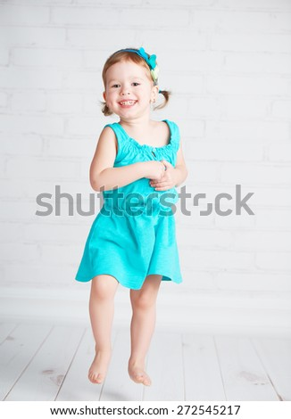 the happy child little girl jumping for joy
