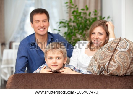 The happy family cheerfully spends time in houses in a room - stock photo
