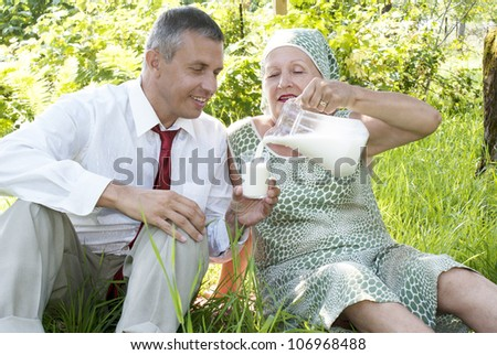 The happy family drinks fresh cow milk in solar summer garden - stock photo