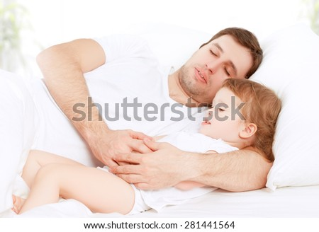 the Happy family father and child baby daughter sleeping in bed - stock photo
