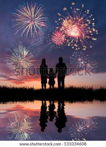 The happy family looks beautiful colorful holiday fireworks in the evening sky with majestic clouds - stock photo