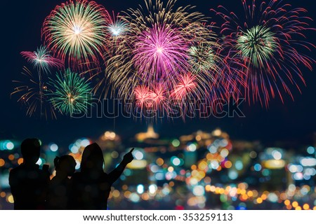 The happy family looks celebration fireworks in the night sky