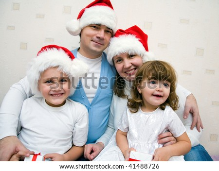 The happy family with two small children in Christmas caps rejoices together