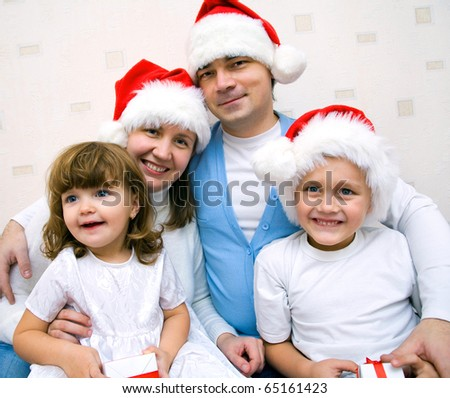 The happy family with two small children in Christmas caps rejoices together - stock photo