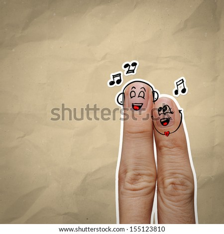 the happy finger couple in love with painted smiley and sing a song on recycle background - stock photo