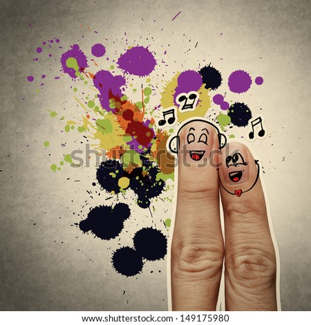 the happy finger couple in love with painted smiley and sing a song on splash colors background - stock photo