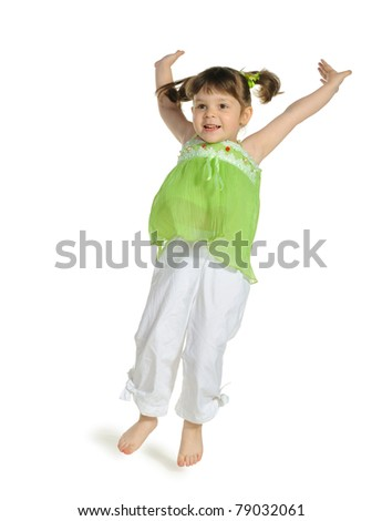 The happy little girl jumps upwards. It is isolated on a white background