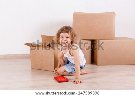 The happy little girl sits in a room near  a lot of the boxes. Moving, purchase of new habitation or repair of a room. - stock photo