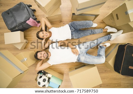 The Happy Man And Woman Lay On The Floor Near Boxes. View From Above