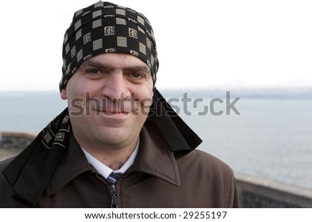 The happy man posing on Sevan background, Armenia - stock photo