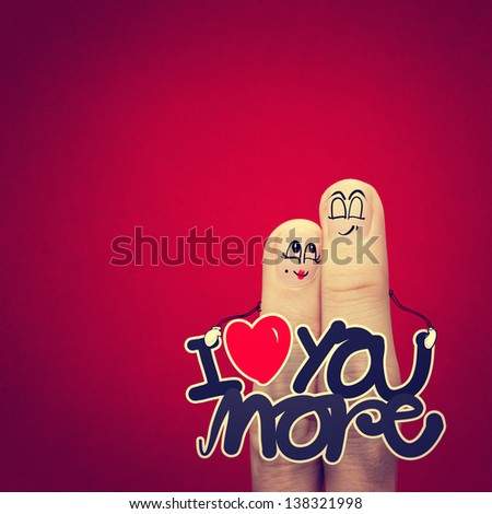 the happy vintage  finger couple in love with painted smiley and hold word love you more - stock photo