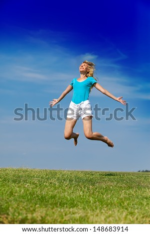 The happy woman jumps in a summer green field against the blue sky