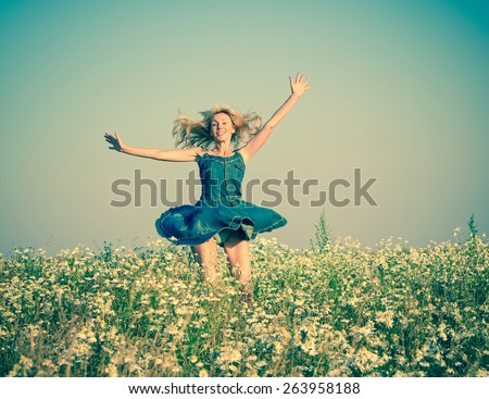 The happy young woman in the field  of camomiles, with a retro effect  - stock photo
