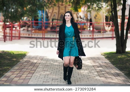 the happy young woman with long hair in a coat walks down the street - stock photo