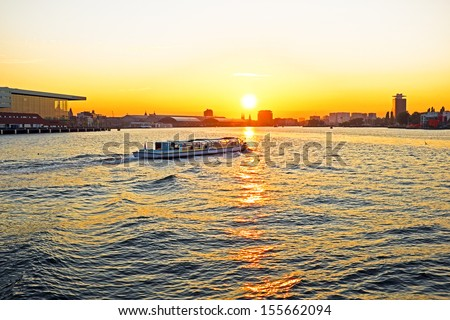 The harbor from Amsterdam with the central station in the background in the Netherlands at sunset - stock photo