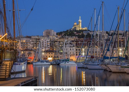 The harbor of Marseilles at night. Looking towards the Cathedral de Notre-Dame-de-la-Garde high on a hill overlooking the city. Cote d'Azur in the South of France.