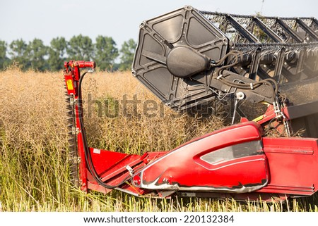 The harvester plowing and collecting on the field - stock photo
