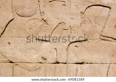The hawk headed god Horus holding a sacred ankh to the face of an ancient egyptian Pharaoh.  Temple of Horus, Edfu, Egypt. - stock photo