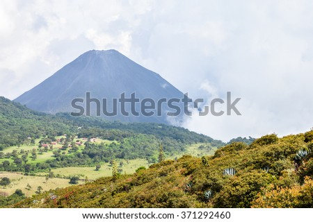 The hazy landscape showing the peak of the active Izalco volcano in El Salvador and the valley beneath it