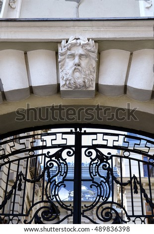 The head of Neptune on a keystone on the archway above a black decorative wrought-iron gate, Bucharest, Romania