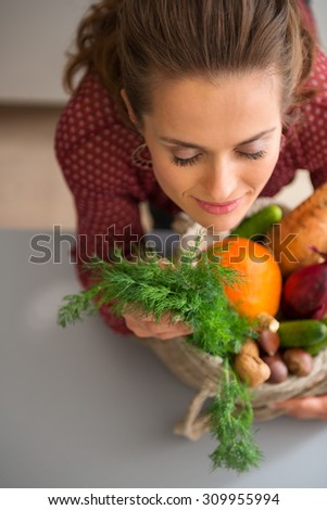 The heady aroma of fresh vegetables. There is nothing quite like it. A woman is closing her eyes with pleasure, smelling the delicate, earthy scent of the fall vegetables she has bought at the market. - stock photo