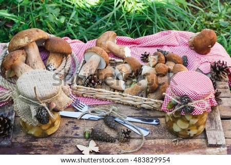 The heap of white mushrooms in the tray with decorations and canned mushrooms on the wooden table