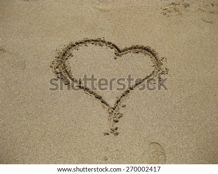 the heart on sand drawn by hand the person