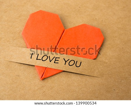 """The heart shape of folded paper on brown screen with """"I love you"""" label - stock photo"""
