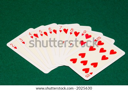 the hearts playing cards on green cloth